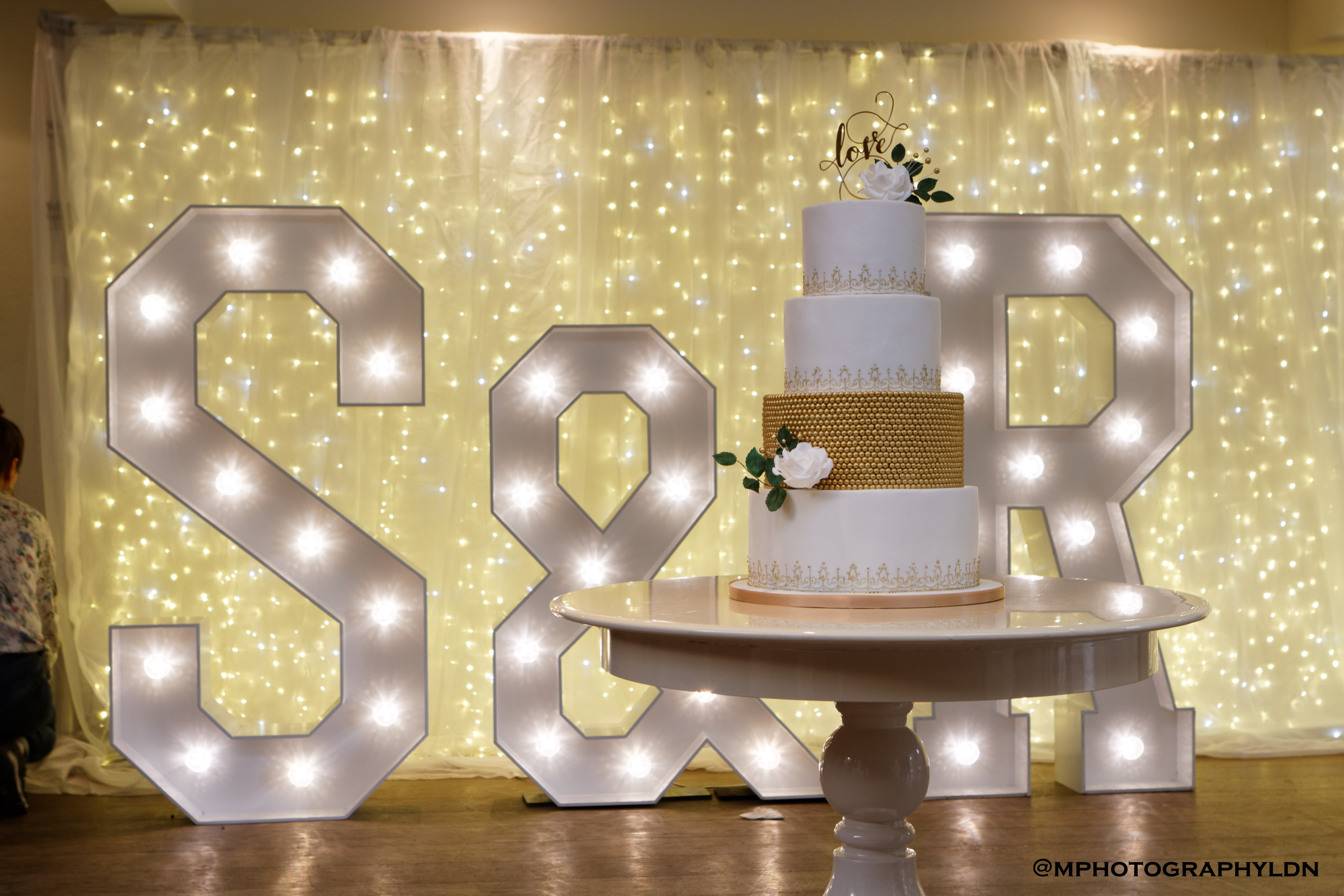 four tiered luxury wedding cake featuring golden sugar pearls and hand-piped bespoke boarders decorated with sugar roses at Stoke Place