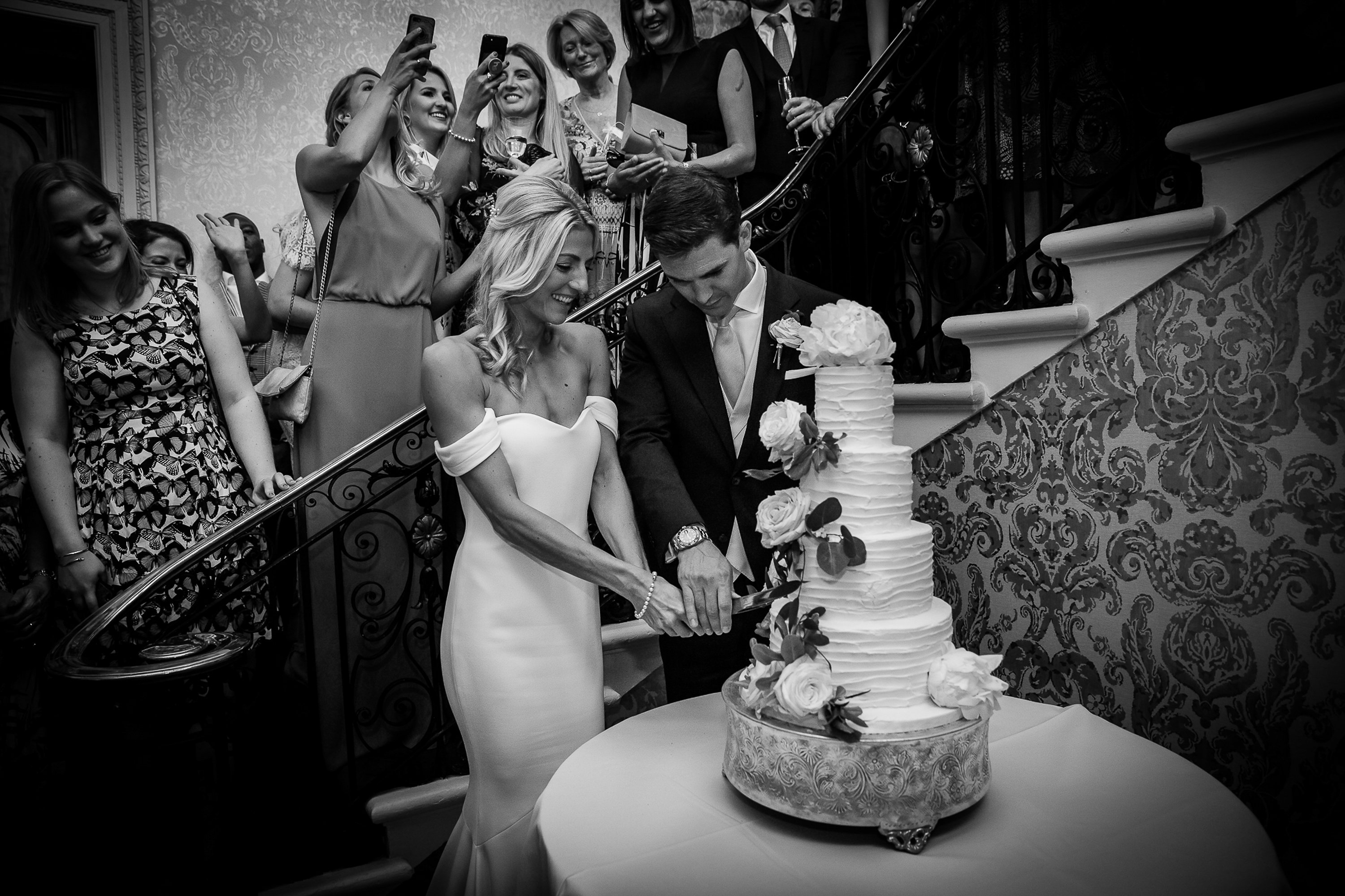 couple cutting their four tiered buttercream luxury wedding cake dressed with fresh flowers at Hedsor House