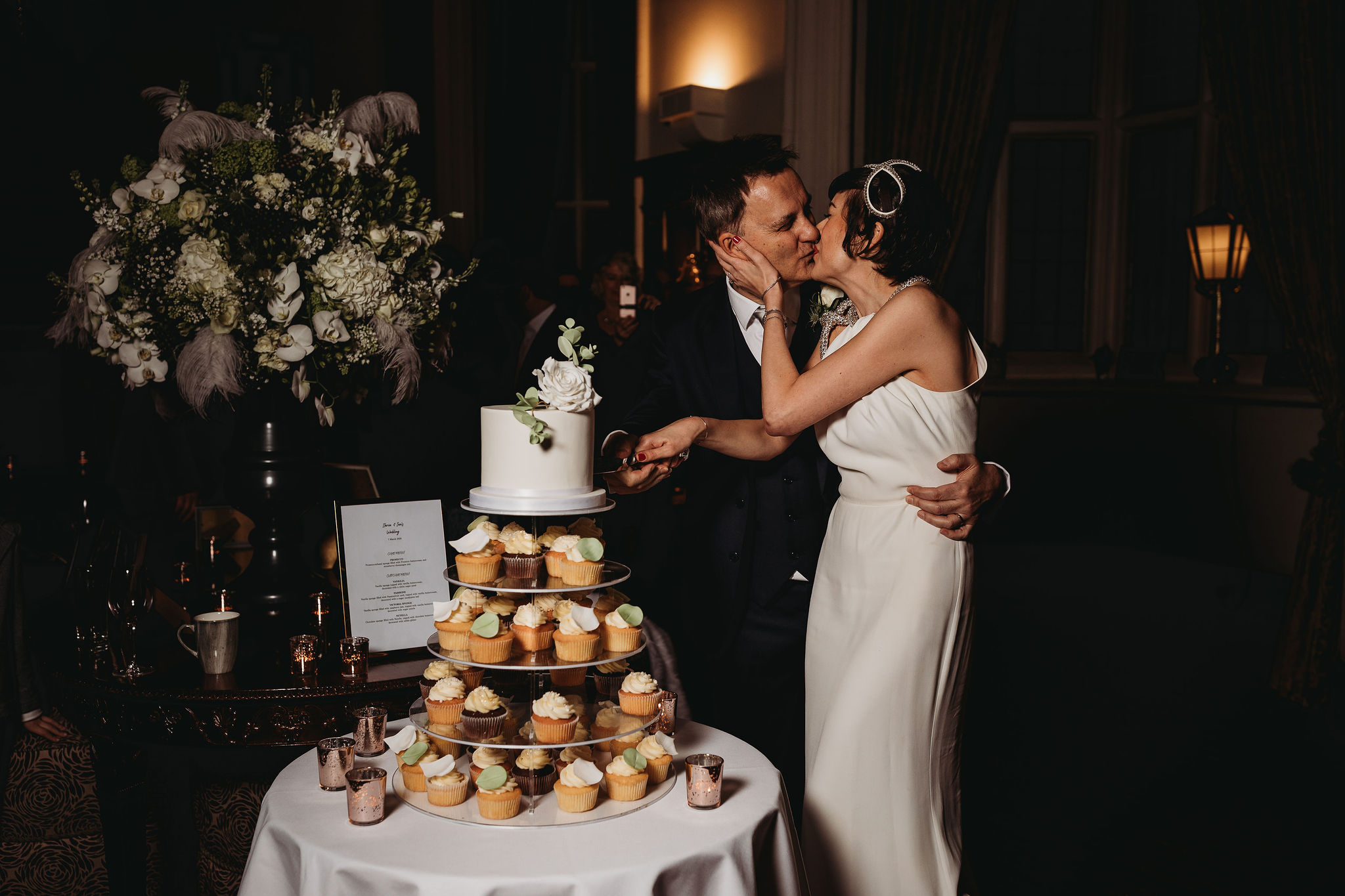 couple cutting top tier of cupcake tower luxury wedding cake decorated with a single sugar rose at Danesfield House. Photo by Thmye Lane Photography