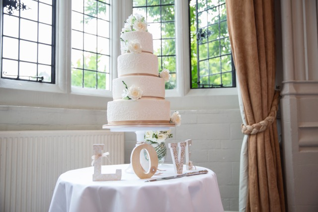 four tiered luxury wedding cake with hand piped lace detailing and sugar roses and fresias at Danesfield House Hotel