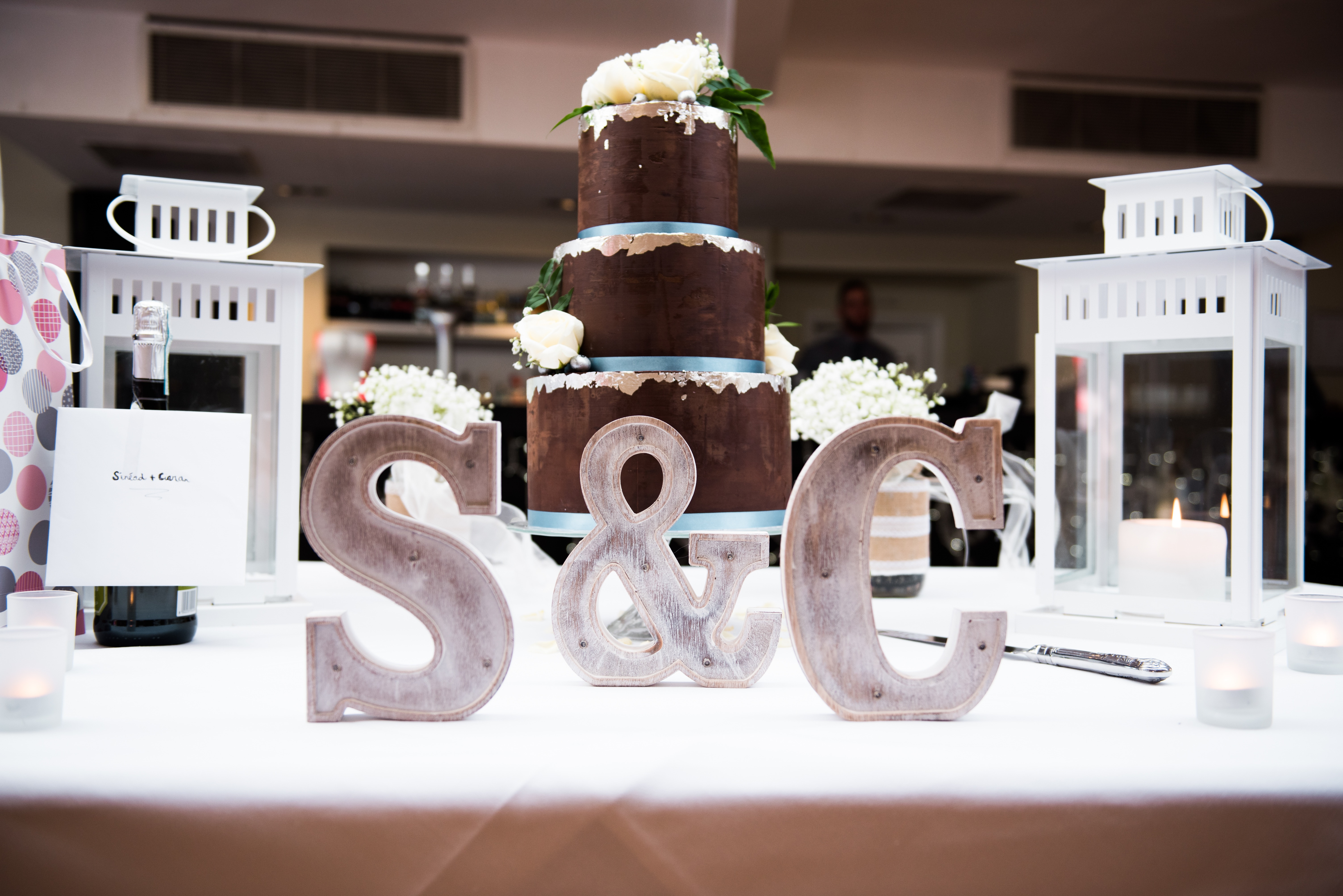 three tiered chocolate ganache luxury wedding cake with edible silver leaf and fresh flowers at Stoke Place